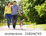 Stock photo hispanic couple taking dog for walk in countryside 218246743
