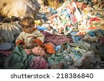 Small photo of KATHMANDU, NEPAL - DEC 22, 2013: Unidentified child is sitting while her parents are working on dump. In Nepal 50,000 children die in 60% of cases from malnutrition.