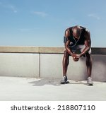 tired young runner leaning over ... | Shutterstock . vector #218807110