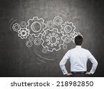 Small photo of Businessman with gears - A concept of well organized work process.