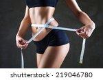 Athletic Slim Woman Measuring...