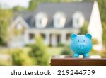 Small photo of Real estate sale, home savings, loans market concept. Housing industry mortgage plan and residential tax saving strategy. Piggy bank isolated outside home on background. Focus on piggybank. Homeowner