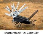 Small photo of multipurpose pocket knife on wood