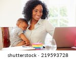 Mother With Baby Working In...