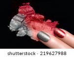 Fingers with trend glitter nails in red and silver. Crushed eye shadow with drops of water. Manicure and makeup concept. Closeup image isolated on black - stock photo