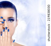 Trendy Blue Makeup. Beautiful young woman with hands on her face covering one eye and mouth. Perfect skin. Nail art and makeup concept. High Fashion Portrait with copy space for text - stock photo