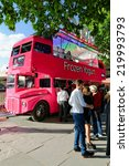 Small photo of LONDON - JULY 1, 2014. Queue in front of an old double decker bus converted in to a pink SNOG Frozen Yogurt shop. The bus is located on the south bank of the Thames river in central London.