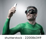 Small photo of Cheerful superhero smiling and taking a selfie with a smartphone.