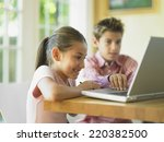 siblings using a laptop together | Shutterstock . vector #220382500