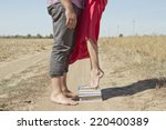 Stock photo a girl stands on a stack of books to reach out and kiss the guy 220400389