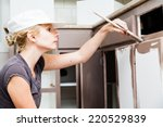 Stock photo closeup of woman holding paint brush and painting kitchen cabinets 220529839
