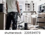 Stock photo mess of all kind of painting equipment in the kitchen and discouraged man 220534573