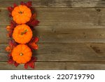 Autumn leaves and pumpkin border against aged wood - stock photo