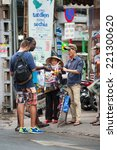 Small photo of HO CHI MINH, VIETNAM - JULY 8, 2014: An unidentified street pedlar offers sunglasses to tourists in Bui Vien Street. Street trading is extremely developed in Vietnam.