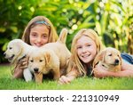 Stock photo adorable cute young girls playing and hugging puppies 221310949