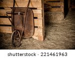 Aged Rusty Barrow in the Wooden Farm Barn. Agriculture Theme. - stock photo
