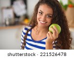 Happy Young Woman Eating Apple...