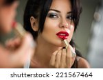 young woman applying lipstick...   Shutterstock . vector #221567464
