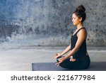 Stock photo latin woman practicing meditation against a urban background 221677984