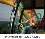 male operator driving excavator on construction building site - stock photo