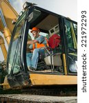 happy male worker operating excavator on construction site - stock photo