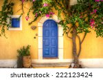 Yellow House With Blue Door In...