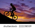 A Silhouette Of A Man Riding A...