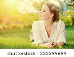 Stock photo beautiful smiling woman lying on a grass outdoor she is absolutely happy 222399694