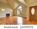 Spacious living room with high ceiling, big arch window, fireplace and new hardwood floor in empty new house.