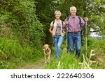 Stock photo happy senior couple doing nordic walking with dog in a forest 222640306