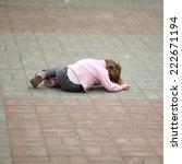 Small photo of alone crying girl lying on asphalt