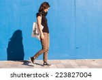 Small photo of Young girl dressed in casual brown chinos, black sneakers and T-shirt walking on a street with blue wall in background.