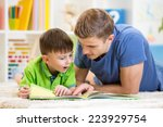Small photo of kid boy and his father read a book on floor at home