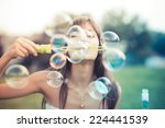 Stock photo beautiful young woman with white dress blowing bubble in the city 224441539