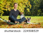 Stock photo two happy dogs with owner sitting on grass in the park 224508529