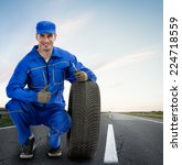 Young Smiling mechanic showing thumbs up next  car tires - road assistance, Towing Service - stock photo