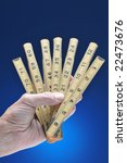 Hand Holding Old Ruler over Blue Gradated Background - stock photo