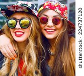 Small photo of Close up fashion portrait of two sisters hugs and having fun together, wearing bright floral hats and stylish mirrored sunglasses, best fiend enjoy amazing time together.
