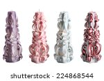 Four Christmas  paraffin colorful candle wax carving, isolated on white background. - stock photo