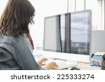 Small photo of Rear view of businesswoman using desktop computer in creative office