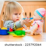 girl feeding a doll at home in... | Shutterstock . vector #225792064