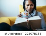 woman drinking tea and reading... | Shutterstock . vector #226078156