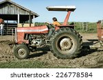 Small photo of Hercul�¢ndia, SP, Brazil - Abr 30, 2006. A normal day at a farm with workers driving a tractor to a barn to feed animals.