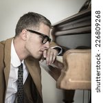 Small photo of Young piano artist without afflatus leaning on piano keyboard