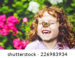 Stock photo laughing girl with a butterfly on his nose 226983934