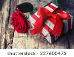 Rose And Present Gift On Woode...