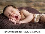 Cute Newborn Yawns Lying On...