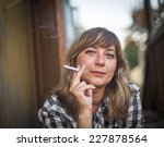 young woman smoking a cigarette. | Shutterstock . vector #227878564