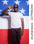 Small photo of Yes sir! Happy young African man in sunglasses holding hand near forehead and smiling while standing against American flag