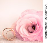 Delicate Wedding background with Rings and Pink Eustoma Flower - stock photo